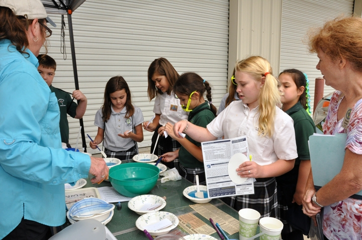 Hazel Wilson, left, helps students create and name hurricanes during an activity.