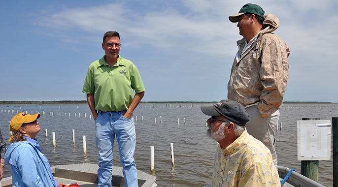 Bill Walton, in green, gives a tour of oyster farms in Alabama earlier this year.
