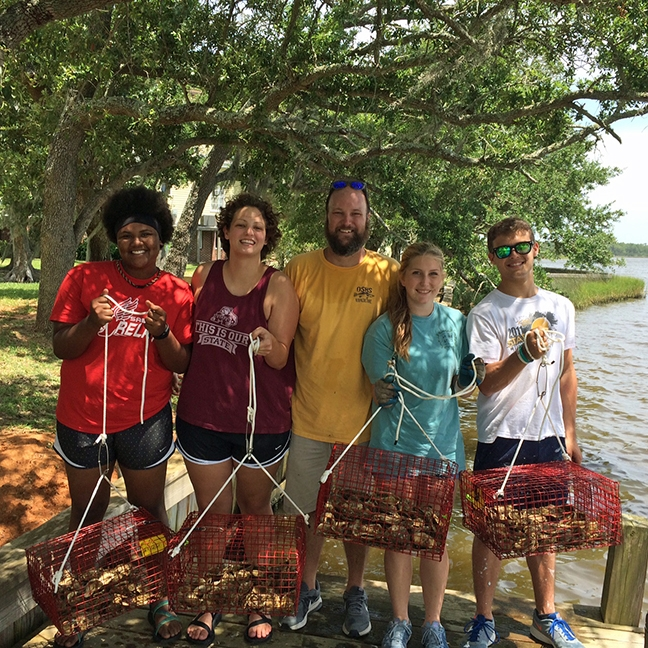 Ocean Springs High School is running a pilot site for the program. Some students, with aquaculture teacher Brian Butler, are pictured here with their oyster gardens.