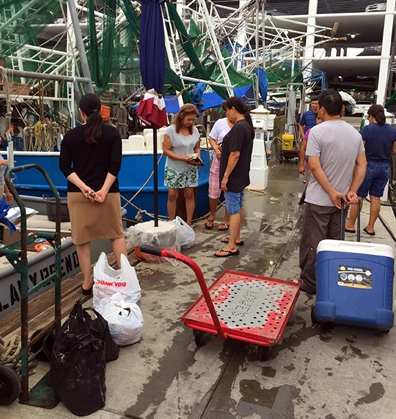 People bring coolers of ice to store the seafood they buy off the boats.