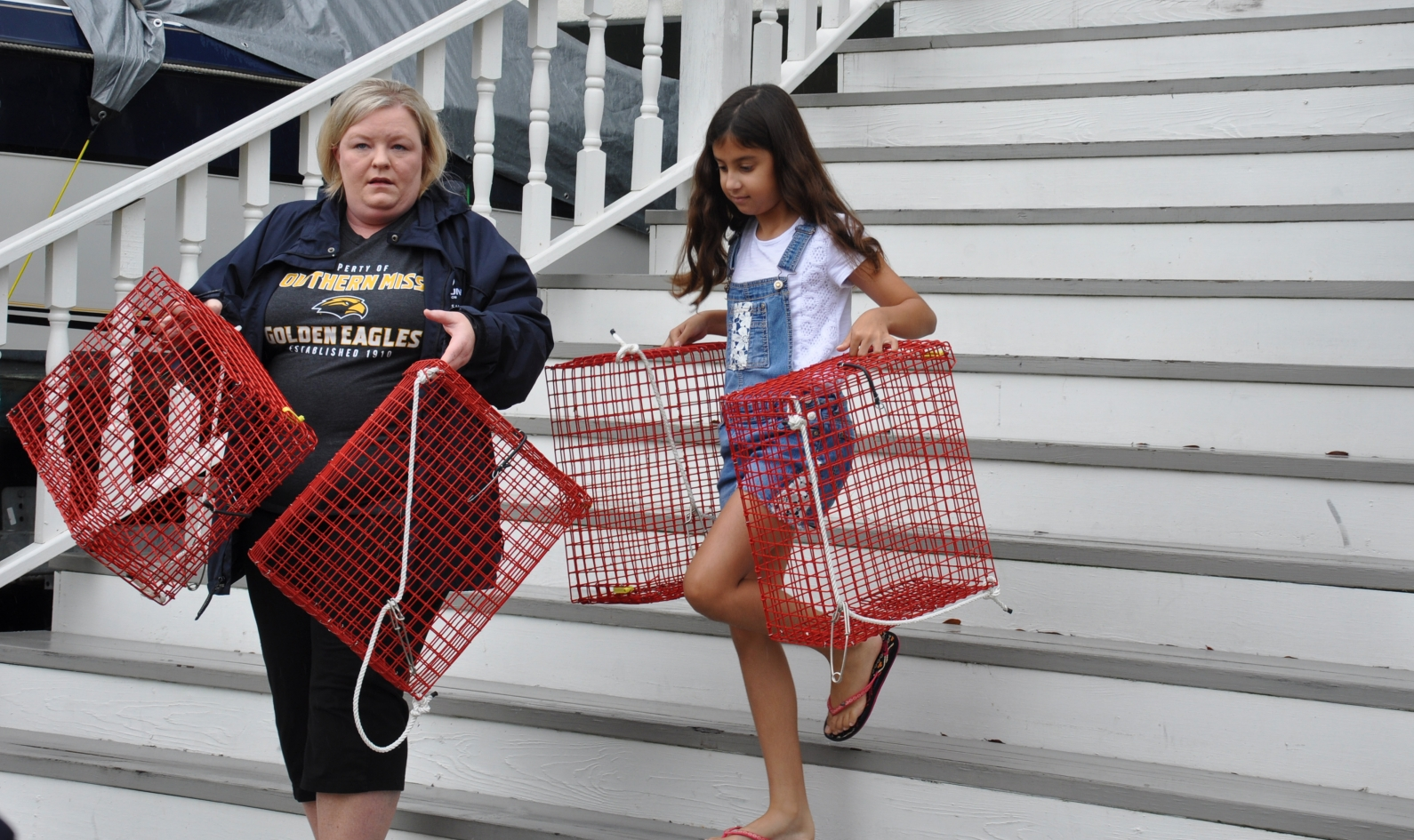 Ocean Springs neighbors Tonya Chancellor, left, and Mari Adlakha carry oyster gardens from a house to a pier.