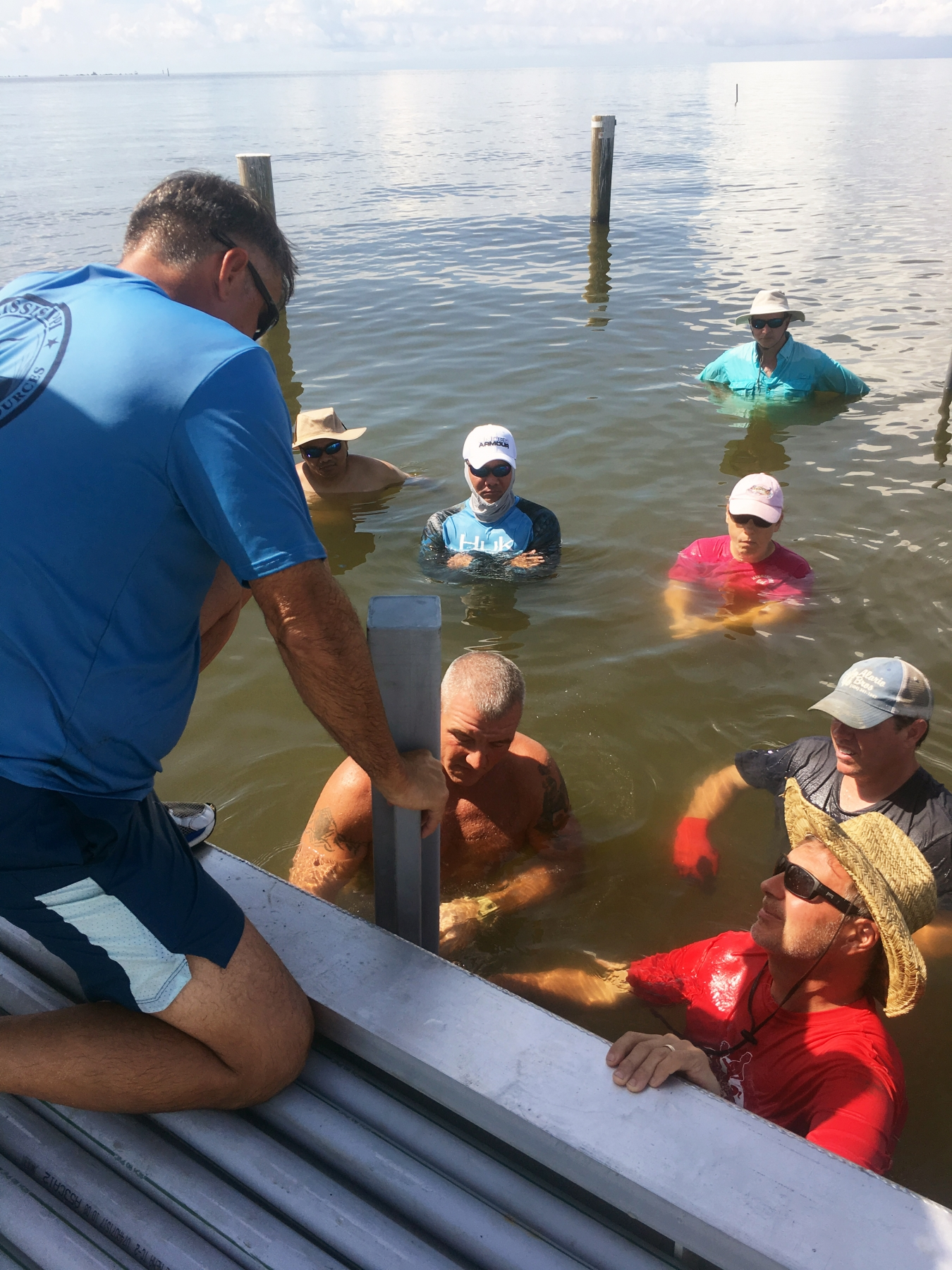 The class installs posts for an adjustable long-line oyster farming system. (Photo by Rusty Grice)