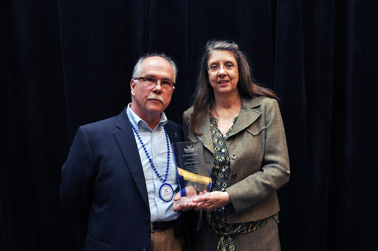 MASGC Director LaDon Swann, left, presents Amy Bridges with a Mississippi-Alabama Sea Grant Excellence Award that honors her late sister, Jenny Cook.